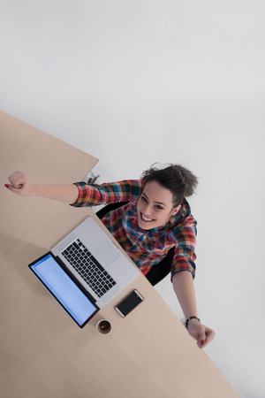 business woman working: top view of young business woman working on laptop computer in modern bright startup office interior
