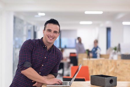 casual office: portrait of young businessman in casual clothes at modern  startup business office space,  working on laptop  computer