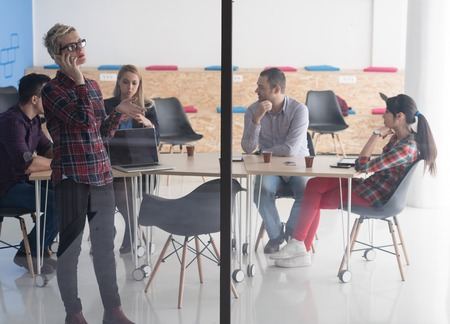 blonde females: business woman in meeting room  speaking by cell phone, people groupbrainstorming in background Stock Photo