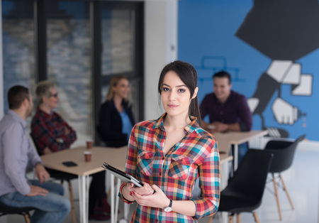 woman in office: portrait of young business woman at modern startup office interior, team in meeting in background