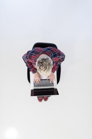 aerial: vista desde arriba de la mujer de negocios joven que trabaja en el ordenador portátil en la oficina moderna interior de inicio brillante, sentado en el suelo