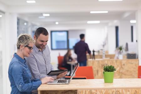 équipe commerciale démarrage sur la satisfaction en plein brainstorming intérieur de bureaux moderne, travaillant sur un ordinateur portable et une tablette informatique Banque d'images