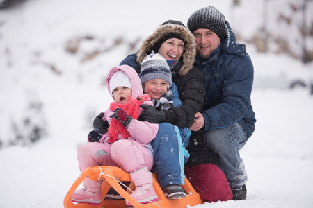 sledging people: happy young family portrait on winter vacation while sitting sledge at  landscape with fresh falling snow Stock Photo