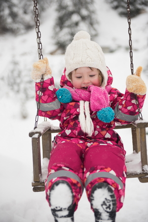 girl on swing: child outdoor in park at winter day with fresh snow, cute little girl swing and playing Stock Photo
