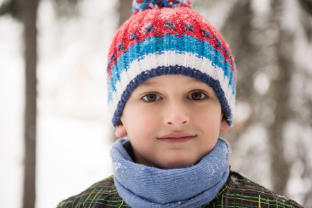 fun day: portrait of happy smiling little boy child outdoors having fun and playing on snowy winter day Stock Photo