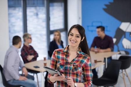 portrait de jeune femme d'affaires au intérieur moderne de bureau de démarrage, l'équipe en réunion en arrière-plan