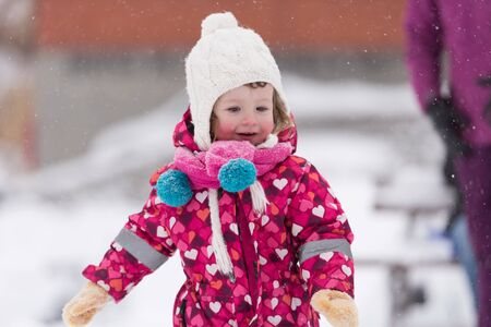 winter fashion: portrait of happy smiling little girl child outdoors having fun and playing on snowy winter day