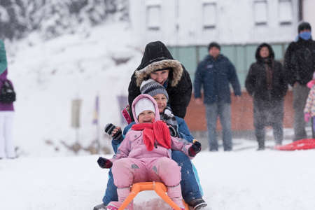 family outside: group of kids having fun and play together in fresh snow on winter vacation