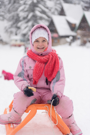 snow break: portrait of cute little girl child sitting on sledges at winter day with fresh snow,  eat cookies and have break