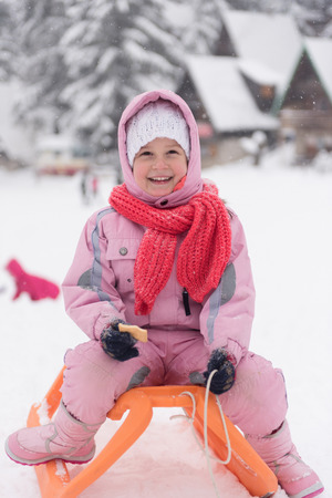 sledging people: portrait of cute little girl child sitting on sledges at winter day with fresh snow,  eat cookies and have break