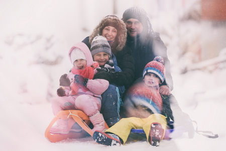 family playing: happy young family portrait on winter vacation while sitting sledge at  landscape with fresh falling snow Stock Photo