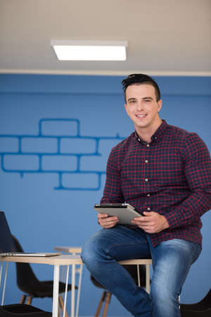 business casual: portrait of young business man in casual clothes sitting on table at  new startup office space