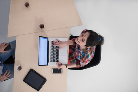 laptop home: top view of young business woman working on laptop computer in modern bright startup office interior