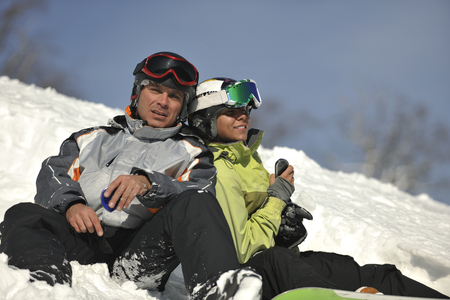 resting: young snowboarders couple relaxing and enjoy on sunny winter day on fresh snow Stock Photo