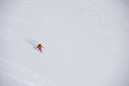piste: extreme freeride skier skiing on fresh powder snow in downhill at winter mountains
