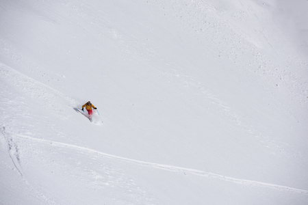 slopes: extreme freeride skier skiing on fresh powder snow in downhill at winter mountains