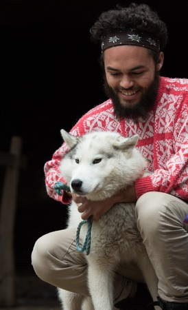 white face: handsome young hipster man playing with white husky dog in front of old vintage retro wooden house