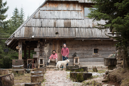 young friends: hipsters couple portrait, two young  man with white husky dog  sitting in front of old wooden retro house Stock Photo