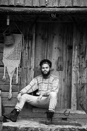fashion clothing: portrait of young hipster,  man with beard in front of old vintage wooden house Stock Photo