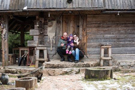 portret van de jonge gezin met kleine kinderen bij elkaar zitten in de voorkant van de oude retro houten huis