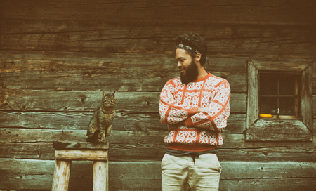 a beard: portrait of young hipster man with beard and cat in front of wooden house