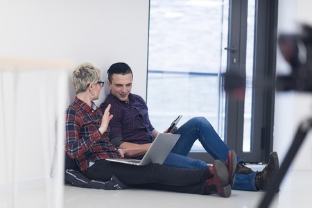 sitting people: startup business and new mobile technology concept with young couple in modern bright office interior working on laptop and tablet computer on new creative project and brainstorming Stock Photo
