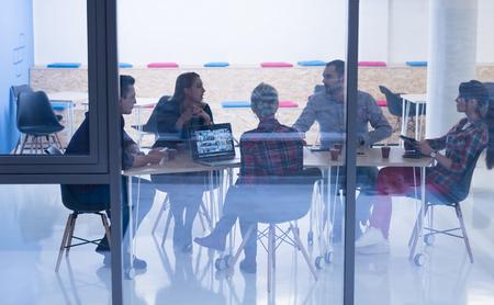 reunion de trabajo: equipo de negocios en el cumplimiento de arranque en la luminosa oficina moderna, entre la lluvia de ideas, trabajando en equipo portátil y la tableta de ordenador