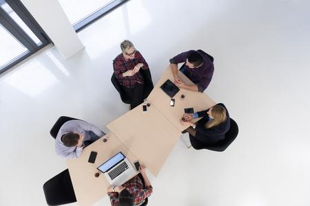 bovenaanzicht van multi-etnische startup mensen uit het bedrijfsleven groep brainstormen bijeenkomst in moderne lichte kantoor interieur