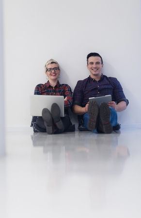 man working computer: startup business and new mobile technology concept with young couple in modern bright office interior working on laptop and tablet computer on new creative project and brainstorming Stock Photo