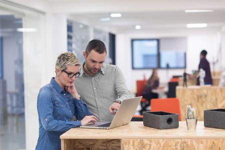 ノート パソコンやタブレット コンピューターで作業して、近代的な明るいオフィス インテリア ブレーンストーミング会議のスタート アップ ビジ