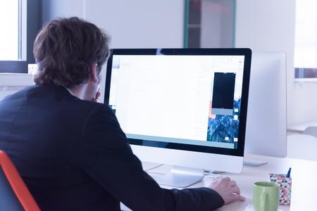 スタートアップのビジネス、近代的なオフィスのコンピューターに取り組んでいるソフトウェア開発者