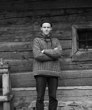 old vintage: portrait of young hipster,  man with nose piercing  in front of old vintage wooden house