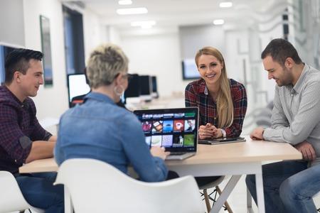 équipe commerciale démarrage sur la satisfaction en plein brainstorming intérieur de bureaux moderne, travaillant sur un ordinateur portable et une tablette informatique