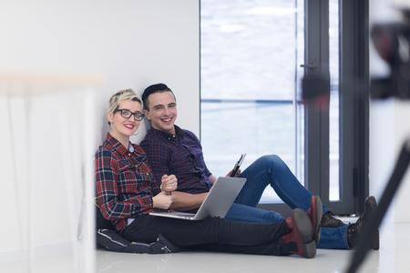 pareja en casa: negocio de lanzamiento y nuevo concepto de tecnología móvil con joven pareja en el interior brillante moderna oficina de trabajo en la computadora portátil y la tableta computadora en nuevo proyecto creativo y de intercambio de ideas Foto de archivo