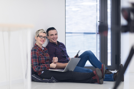 couple home: startup business and new mobile technology concept with young couple in modern bright office interior working on laptop and tablet computer on new creative project and brainstorming Stock Photo