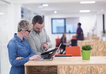empresas: equipo de negocios de inicio en el cumplimiento de moderno y luminoso de reflexión interior de la oficina, trabajando en equipo portátil y la tableta de ordenador Foto de archivo