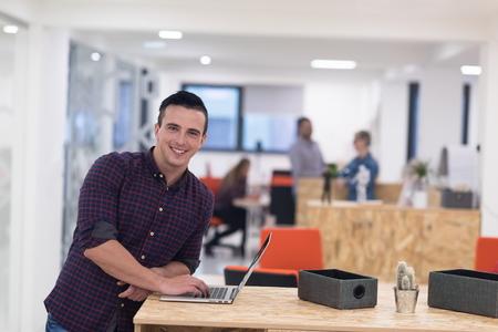 노트북 컴퓨터에서 작동하는 현대 시작 비즈니스 사무실 공간에서 캐주얼 의류에서 젊은 사업가의 초상화