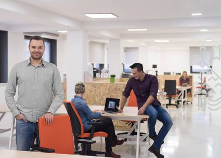 happy workers: portrait of young businessman in casual clothes at modern  startup business office space,  team of people working together in background