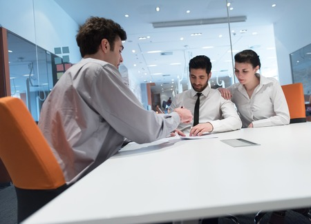 life partner: signing contract on partners back, young couple on business meeting with life insurance and bank loan agent at modern office interior