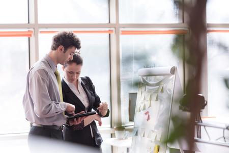 jeunes projets réussis démarrage d'affaires du groupe de personnes de planification de remue-méninges et de prendre des notes à tableau blanc flip et le contrôle ordinateur tablette à l'intérieur du bureau moderne et lumineux