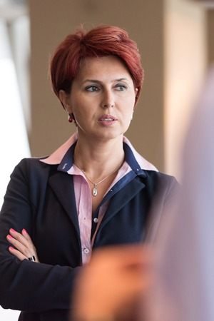 executive women: redhair senior  business woman portrait at corporate office interior standing in fton of her team as leader