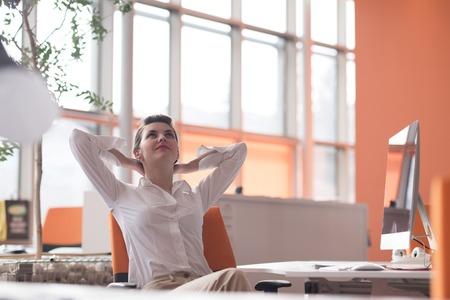 Glückliche junge Frau Geschäft entspannend und insiration Geting während bei modernen hellen starup Büro-Interieur auf dem Desktop-Computer Standard-Bild - 56638787