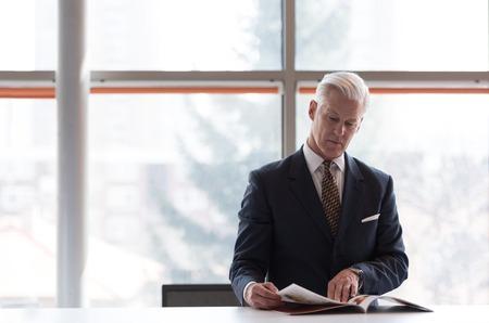persona leyendo: hombre de negocios de alto la lectura de revistas en la oficina brillante moderna Foto de archivo