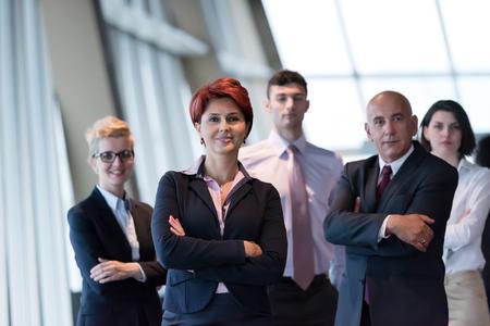 los diversos grupos de negocios de pie juntos como equipo en la oficina moderna interior brillante. Mujer mayor pelirroja delante de líder