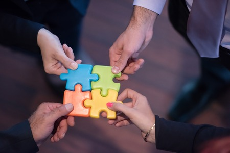 business help: diverse business people group assembling jigsaw puzzle and represent team support and help concept, top view perspective at modern bright office interior