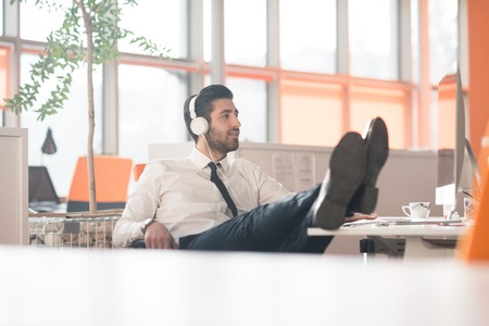happy worker: happy young arabian  business man with beard  listening music on headphones at modern startup office