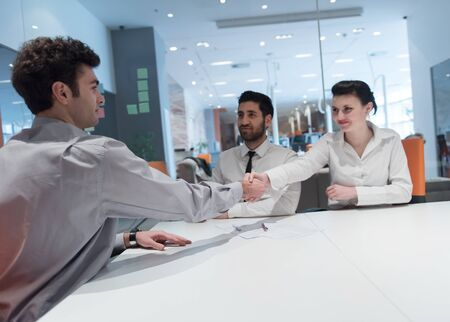 bank interior: signing contract on partners back, young couple on business meeting with life insurance and bank loan agent at modern office interior