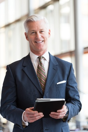 phone professional: handsome senior business man with grey hair working on tablet computer at modern bright office interior