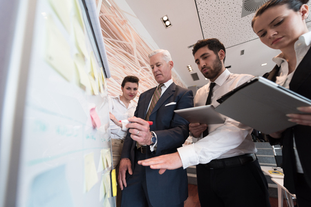 presenting: business people group brainstorming on meeting and businessman presenting ideas and projects on flipboard to senior ceo manager, boss giving task and projects to employees
