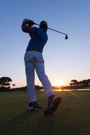 plan �loign�: golfeur hitting long shot avec chauffeur sur le cours au beau coucher de soleil